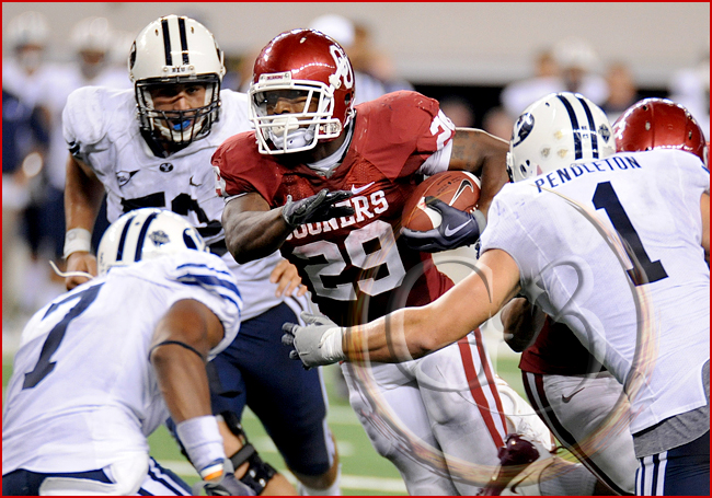 Oklahoma running back Chris Brown #29 carries the ball as he is met by Brigham Young defensive back Brian Logan #7 and Brigham Young linebacker Jordan Pendleton #1